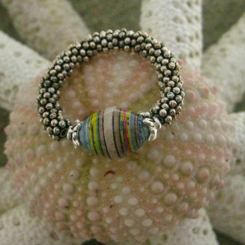 A single paper bead made into a ring using elastic and spacers