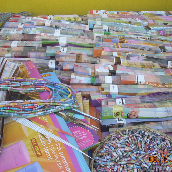Strips of paper from magazines neatly cut up ready to be rolled